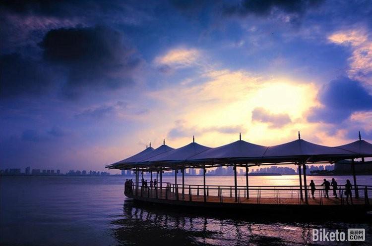 夕阳渐渐西下,延伸到湖中的水亭里,游人也渐散去.